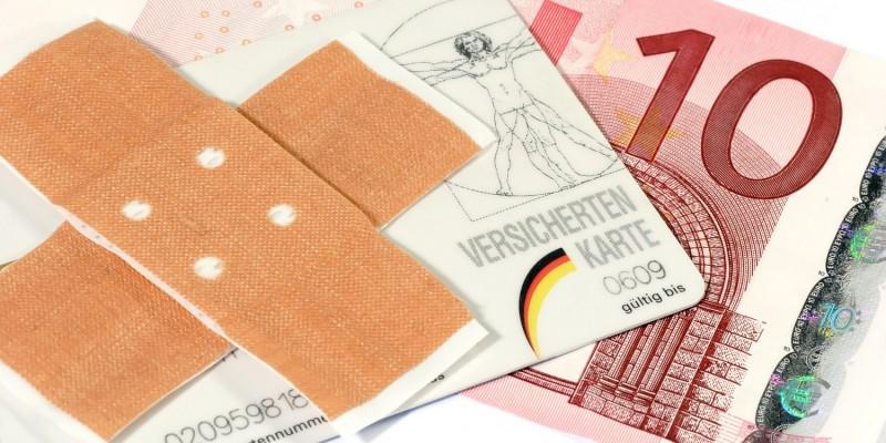 Versichertenkarte mit Pflaster und Geldschein